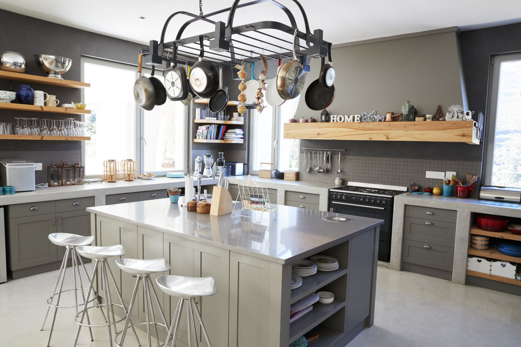 You can maximize storage space in your kitchen by adding a kitchen island with shelving, hanging pots and pans from the ceiling, and adding additional shelving in used spaces.