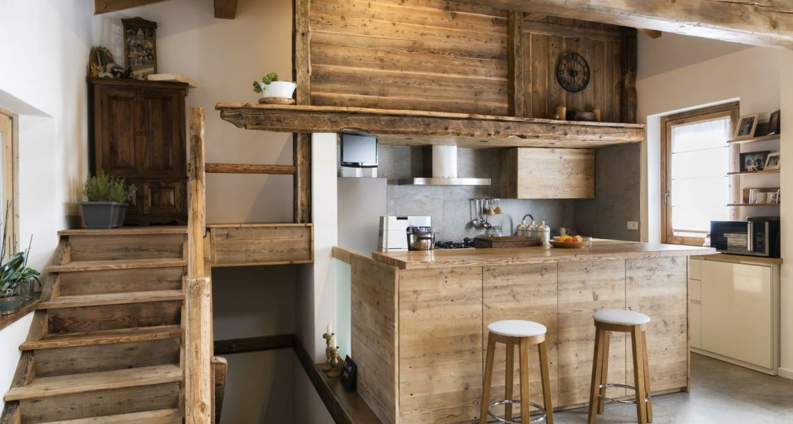 A cottage style kitchen can feature a charming appeal. This kitchen design features a wooden staircase, wooden bar stools, and even wooden storage cabinets.