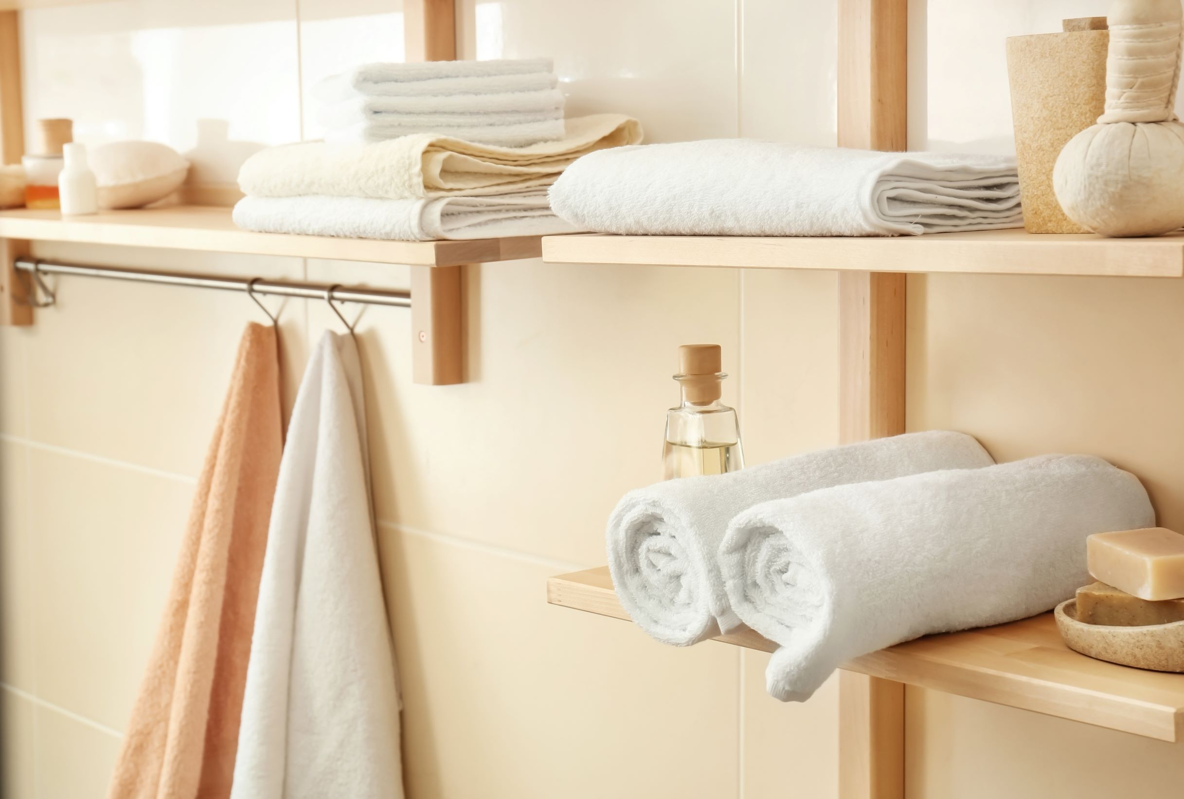 Smart bathroom storage solutions include using the walls to create shelves for towels.